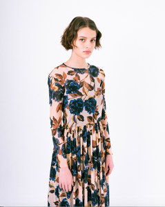 Side profile view of blue floral print on tan mesh overlay a-line dress with long sleeves over slip dress on woman
