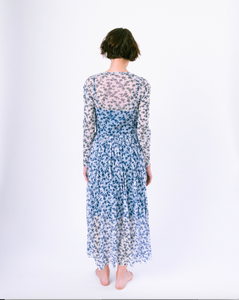 Back view of long sleeve blue and white floral a-line dress with mesh overlay over slip dress on woman