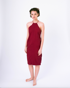 Front of dark red halter dress with open back & crossed straps on woman