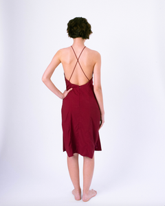 Back view of dark red halter dress with open back & crossed straps on woman
