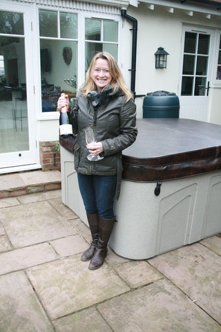The lucky winner standing next to her new hot tub