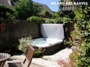 Mr & Mrs R Eaves hottub with a cover in their garden next to a big stone wall