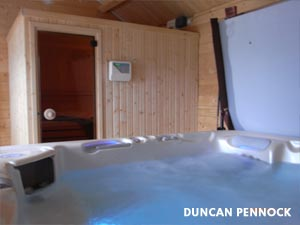 Duncan Pennocks hottub filled with water, with cover, standing next to a sauna