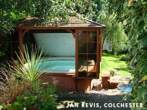 Jan Revis roofed hottub standing in his garden full with many plants