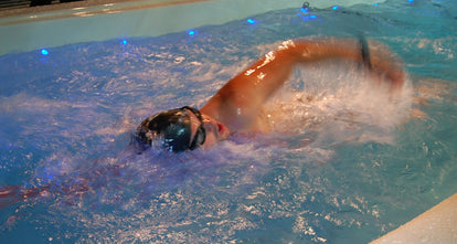 Young man exercising in a swim spa