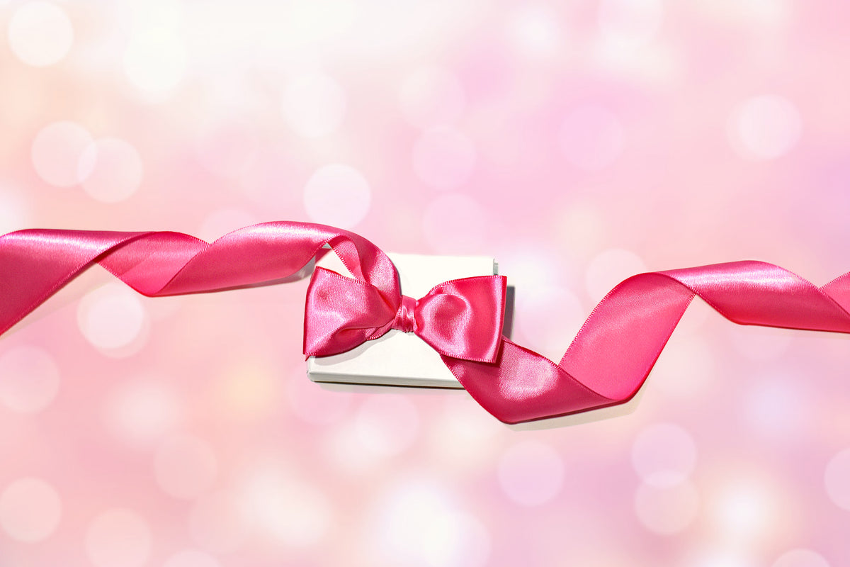 White jewelry gift box with pink bow.