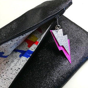 Close up Glitter Disco Envelope Clutch Bags open with lightning bolt tags and 80's print lining