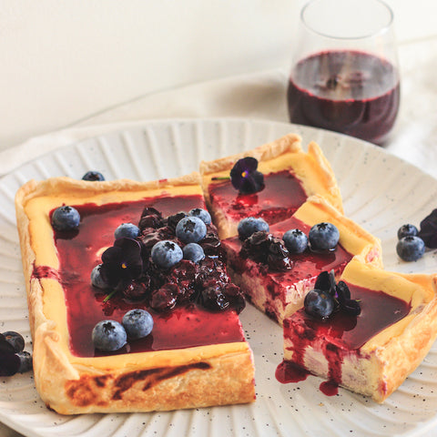 A square cheesecake on white plate with berries on top.