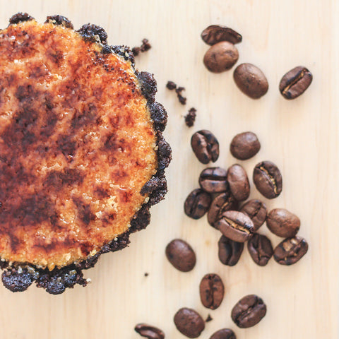 Coffee flavoured creme brulee with coffee beans sprinkled next to it.