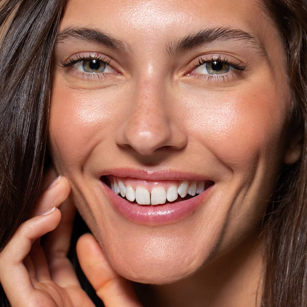 six gldn model smiling with glowing skin and rosy cheeks