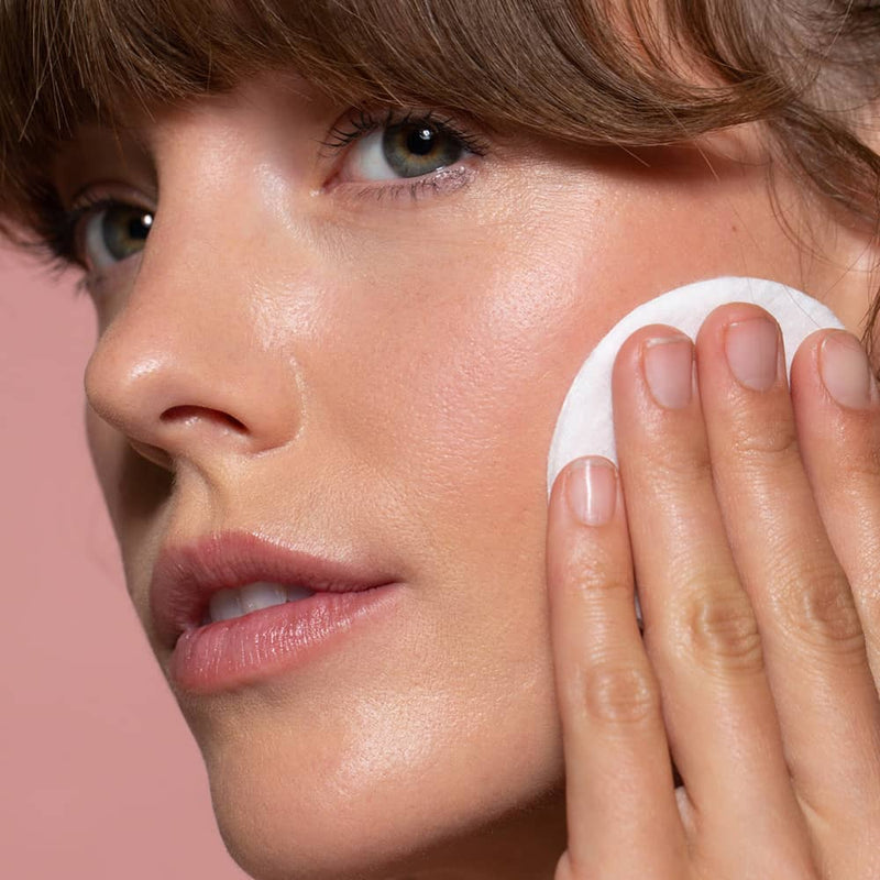 Close up of a Six Gldn model using the Botanical Toner on her cheek with a white cotton pad against a light pink background