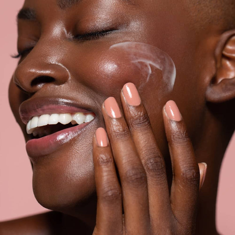 Six Gldn model spreading some Essential Moisturizer on her cheek with glowing skin and a smile