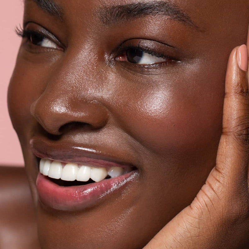 Close up face photo of a Six Gldn model with one hand to her face looking to the side as she smiles with a light pink background