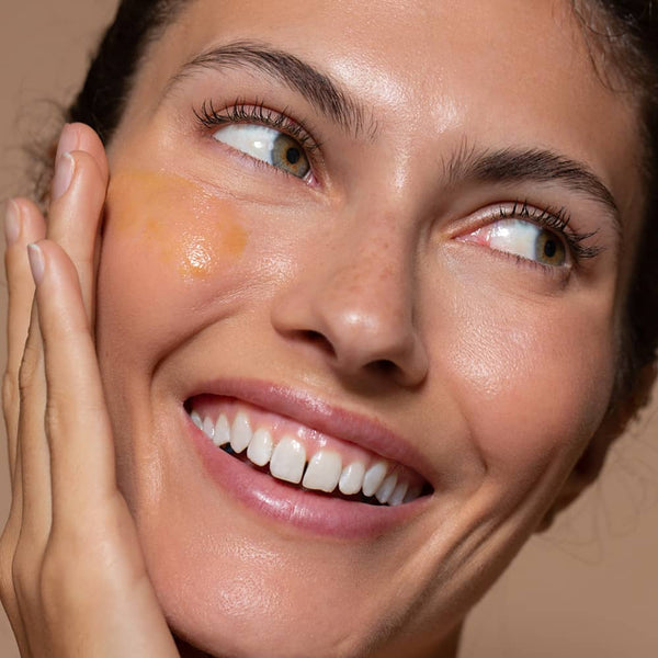 A close up photo of a Six Gldn model applying the Daily Vitamin C Radiance Serum to her cheek with one hand while she is smiling and looking to the side