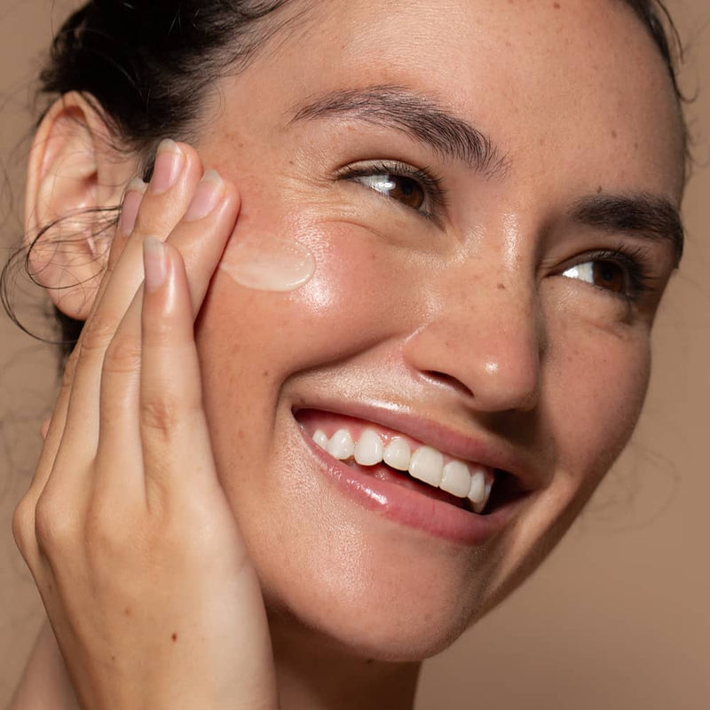 Close up photo of a Six Gldn model applying the Essential Moisturizer to her cheek with her fingers while she is smiling and looking to the side