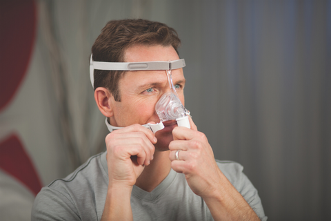 Man adjusts his CPAP mask