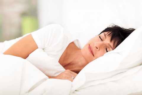 A mature woman sleeping in her bed