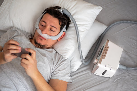 man using a CPAP machine in bed