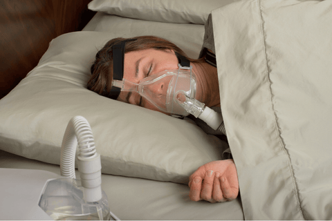 Woman wearing a CPAP mask while sleeping