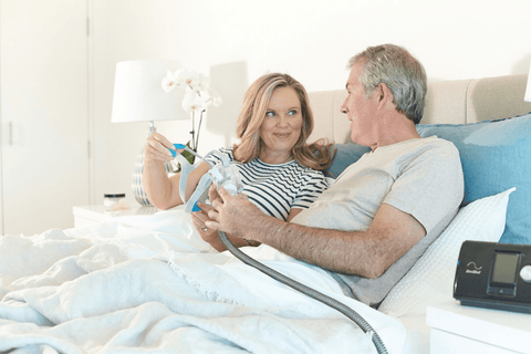 A couple holding a CPAP mask while getting ready to sleep