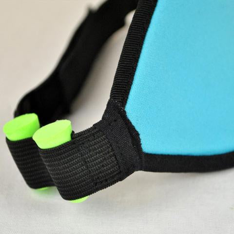 Closeup view of Blockout Shade Mask in turquoise color with green earplugs on the side.