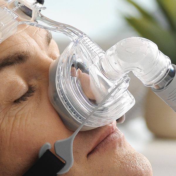 Closeup view of man's face sleeping with clear Zest Q Premium Nasal CPAP Mask with black Headgear by Fisher & Paykel.