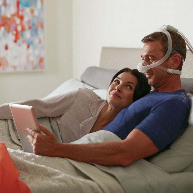 Couple in bed and man using DreamWisp Nasal Mask while reading.