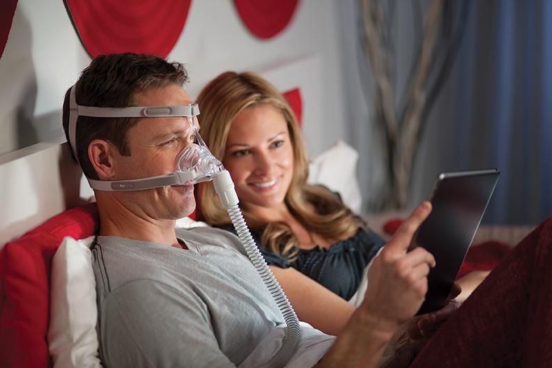 Man reading tablet while wearing the Nasal Pico Mask.