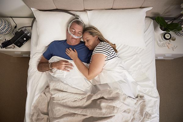 Man sleeping with ResMed AirFit P30 and his partner on the side
