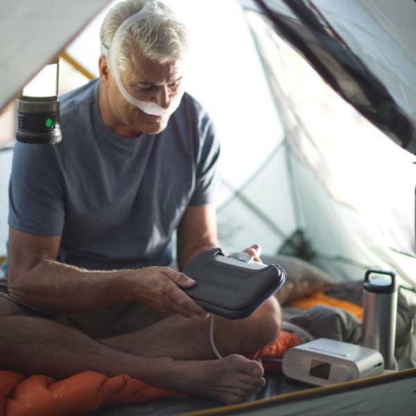 Man using the Respironics white travel battery to power the DreamStation CPAP Machine