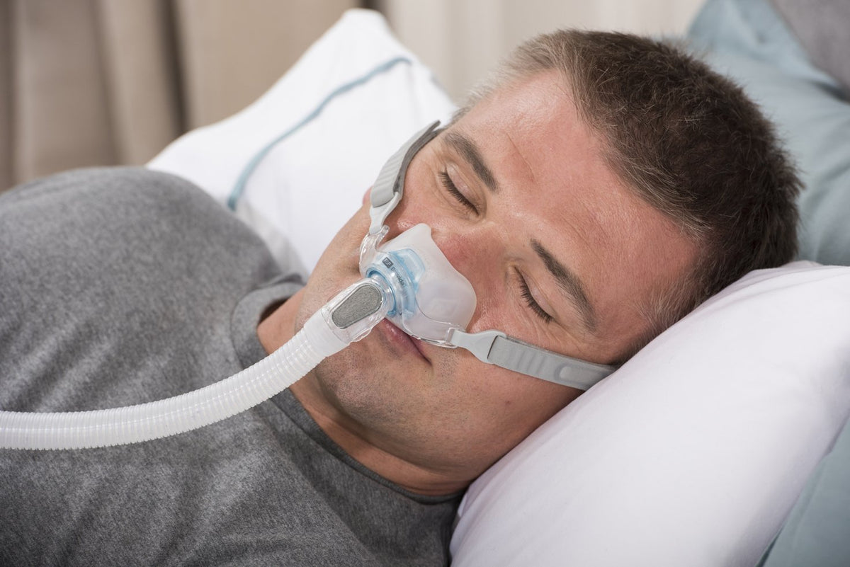 Man sleeping with Brevida Nasal Pillow CPAP Mask
