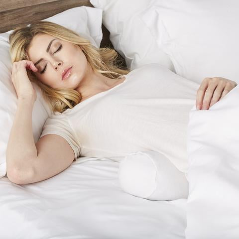 Woman sleeping with Comfort Bolster White Pillow under her low back.