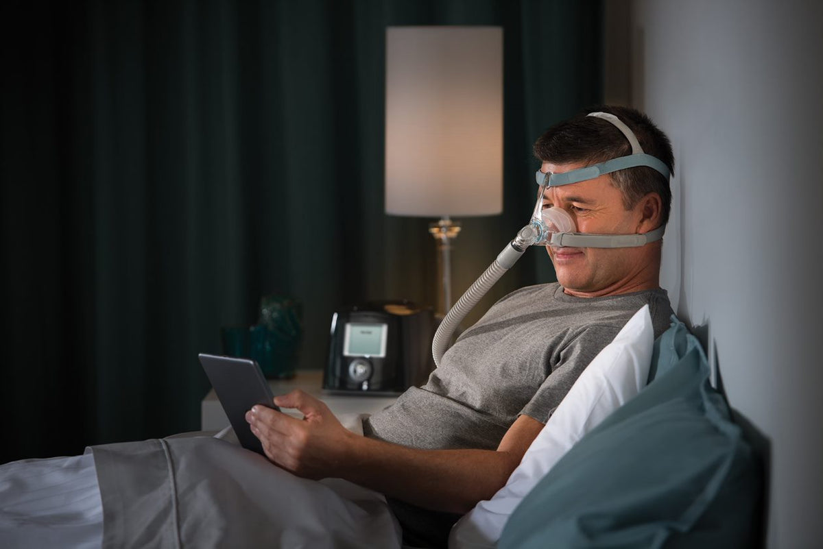 Man reading from his tablet while wearing Eson 2 Mask and headgear.