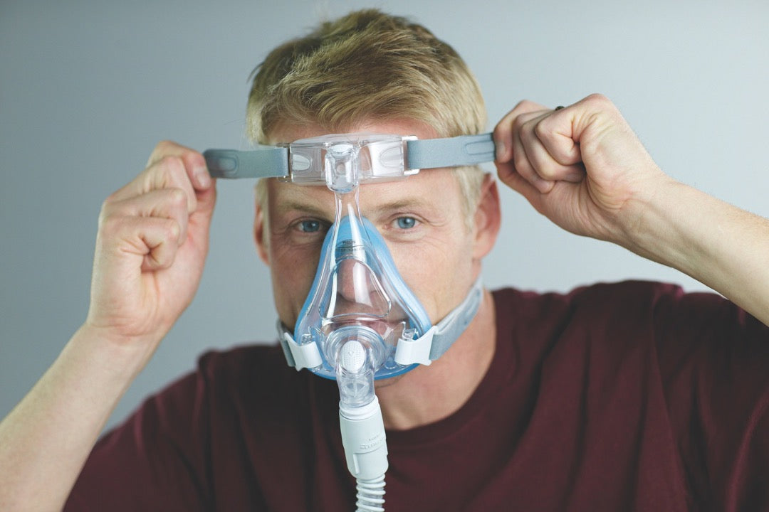Man adjusting grey straps of Amara Full Face CPAP Mask with Gel & Silicone Cushions