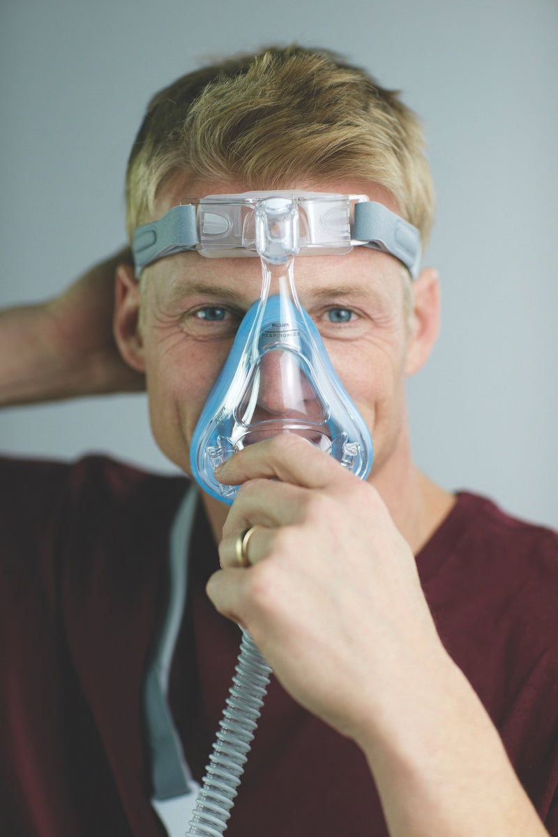 Man grabbing the Amara Full Face CPAP Mask with Gel & Silicone Cushions