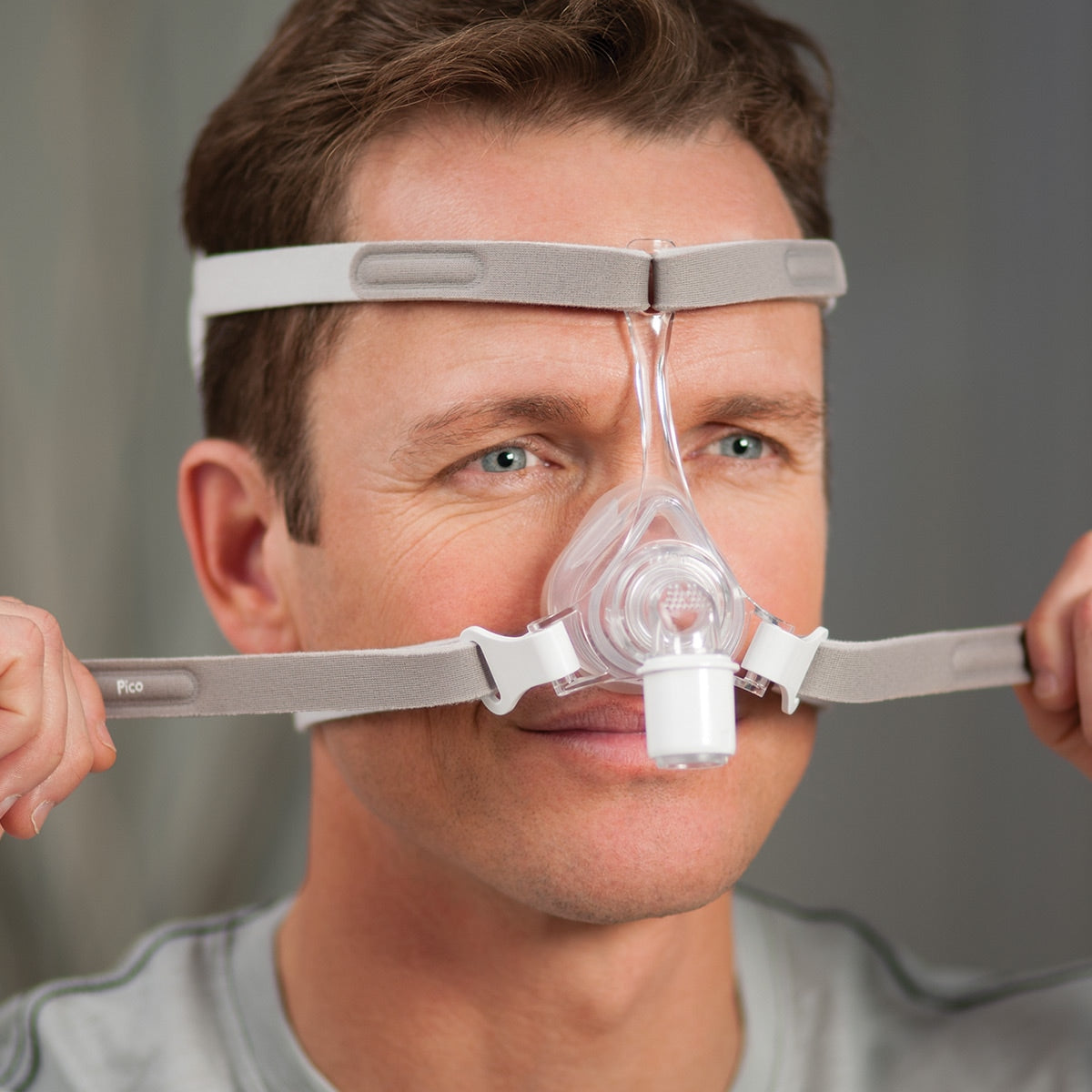 Man adjusting the straps from the grey headgear for Pico Nasal CPAP Mask Fit Pack by Phillips Respironics.