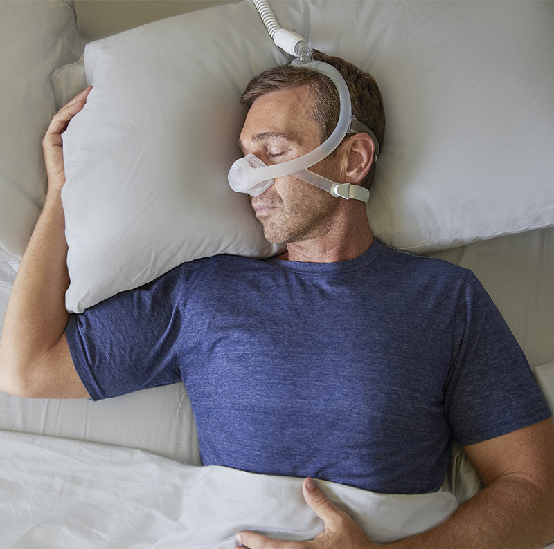 Man comfortably using DreamWisp Nasal Mask while sleeping.