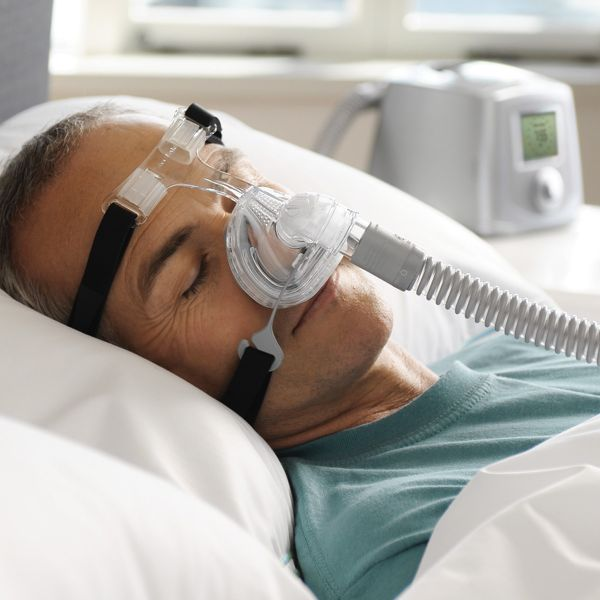 Man sleeping with clear Zest Q Premium Nasal CPAP Mask with black Headgear by Fisher & Paykel.