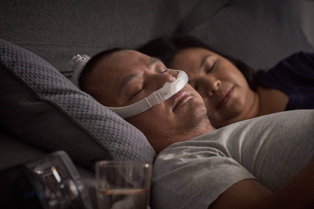 Man sleeping with ResMed AirFit P30 and his partner on the side.