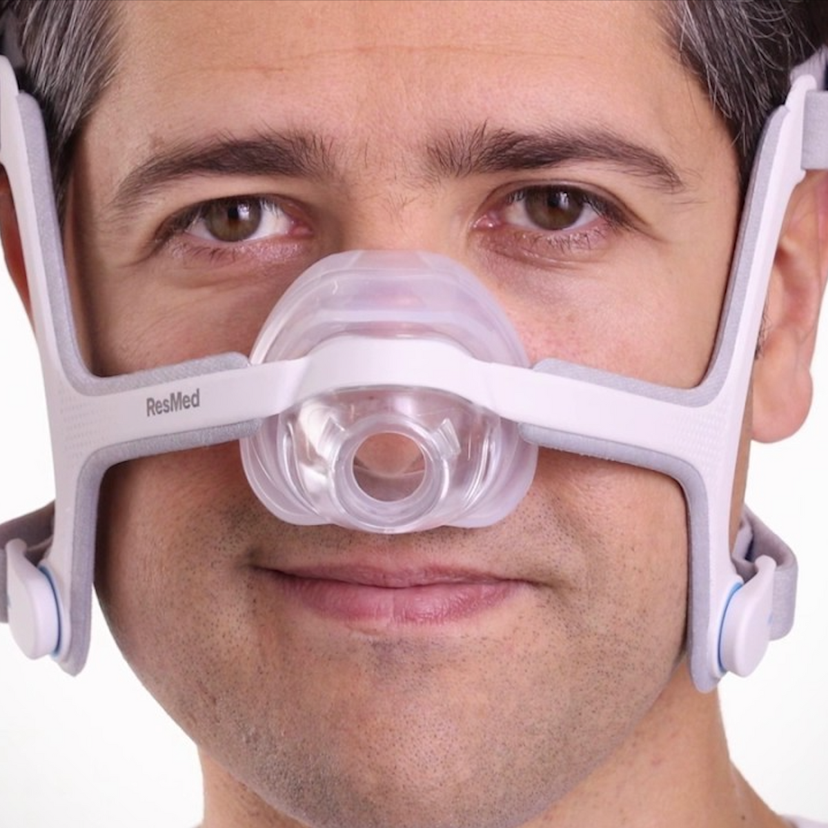 Man adjusting headgear of ResMed AirFit N20 with cushion.