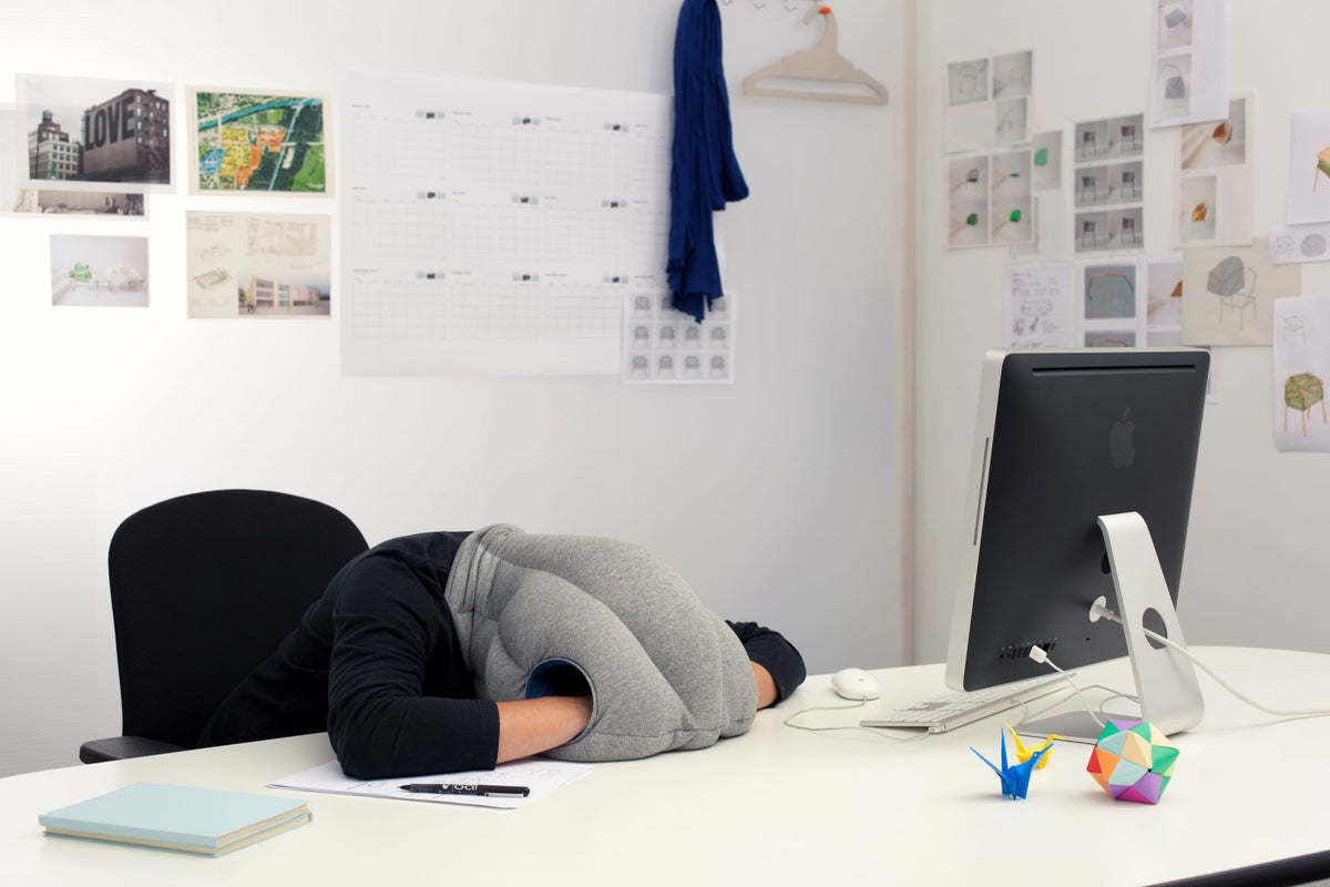 Woman Sleeping On Desk With Original Immersive Napping Pillow.