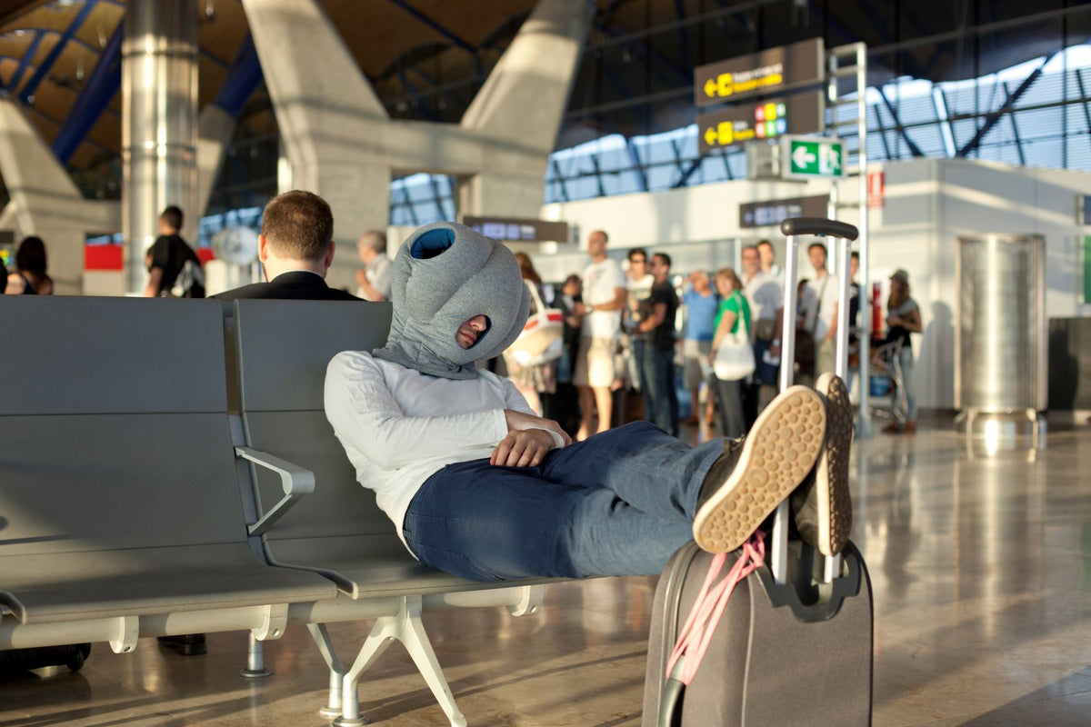 Man Sleeping In Airport With Original Immersive Napping Pillow.