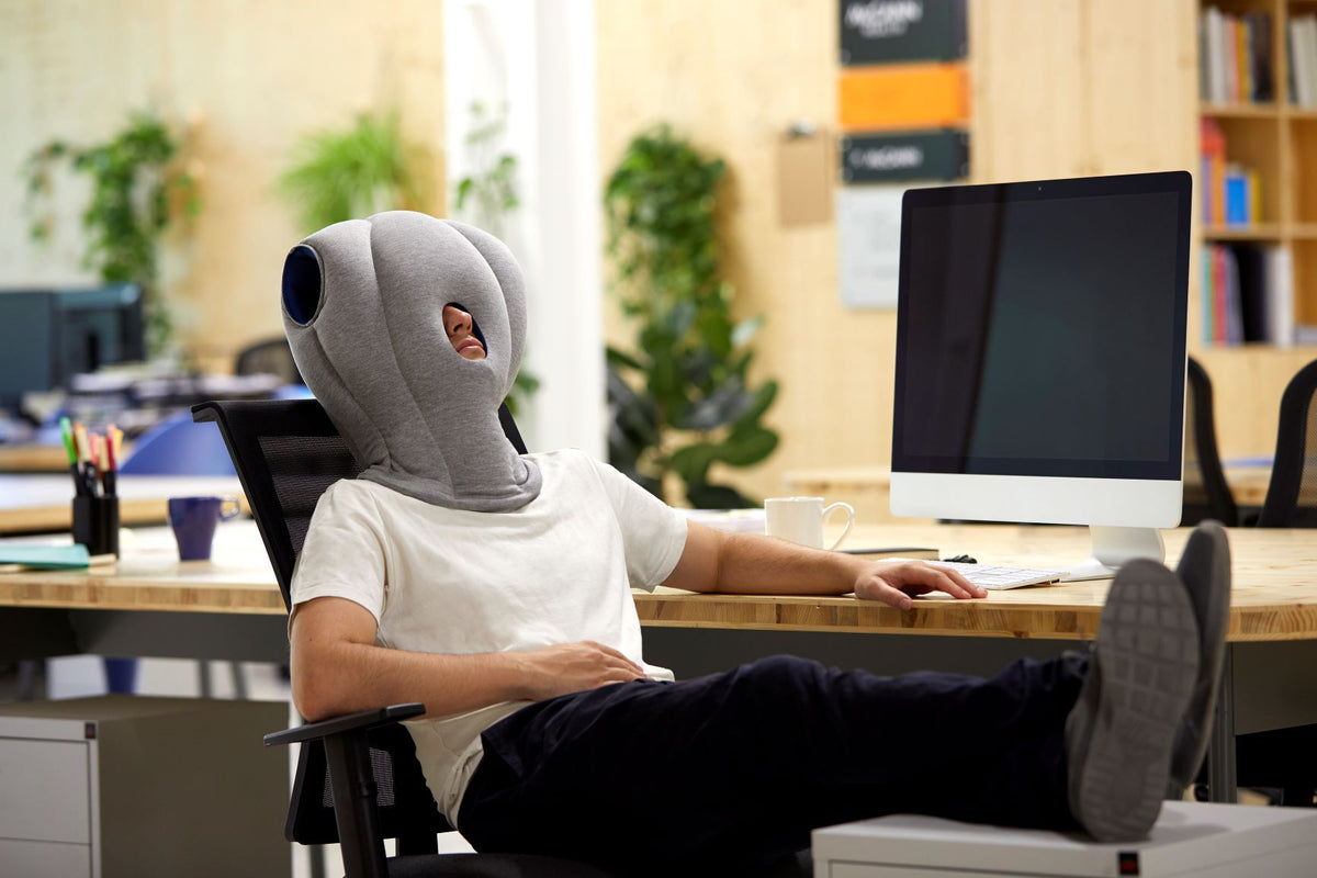 Man Sleeping On Desk Chair With Original Immersive Napping Pillow.