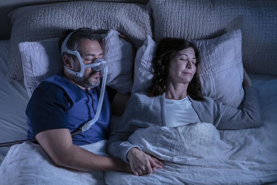 Couple sleeping and man wearing CPAP Airtouch mask.