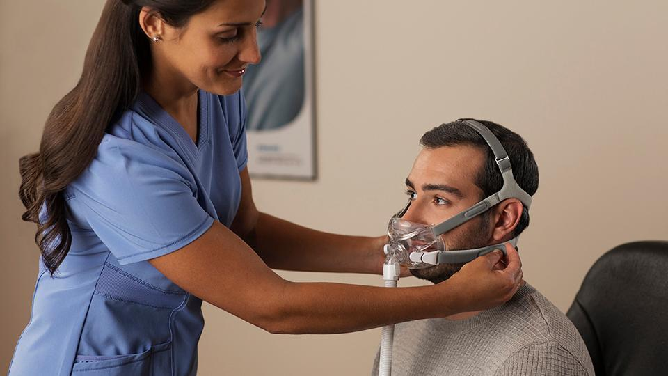 Nurse fitting the Respironics Amara View mask to the man sitting in front of her.