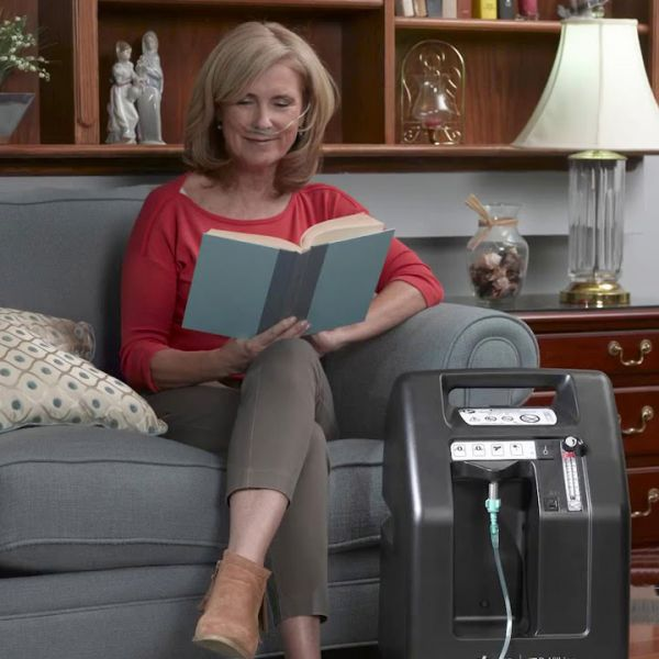Woman reading a book while using Compact 525DS Oxygen Concentrator Bundle - 5 LPM