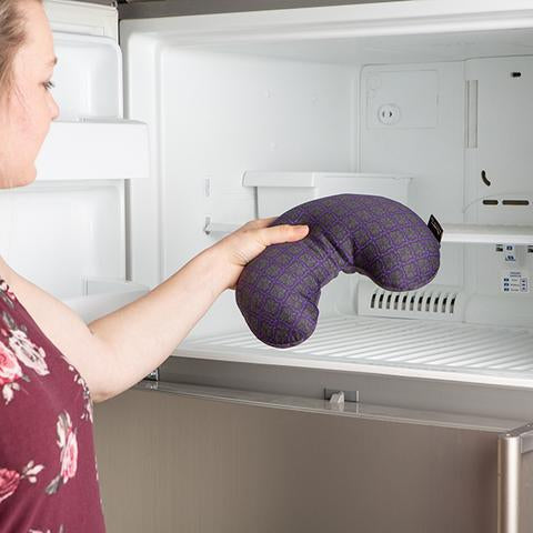 Female placing Compack Neck Pillow by Bucky in the freezer.
