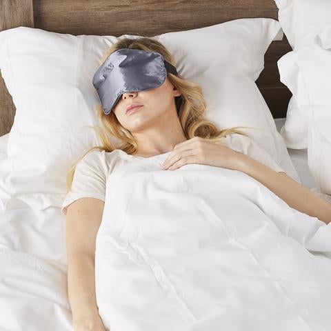 Woman sleeping in bed with Serenity Spa Mask in gray color by Bucky.