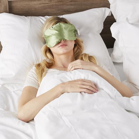 Woman sleeping in bed with Serenity Spa Mask in sage color by Bucky.