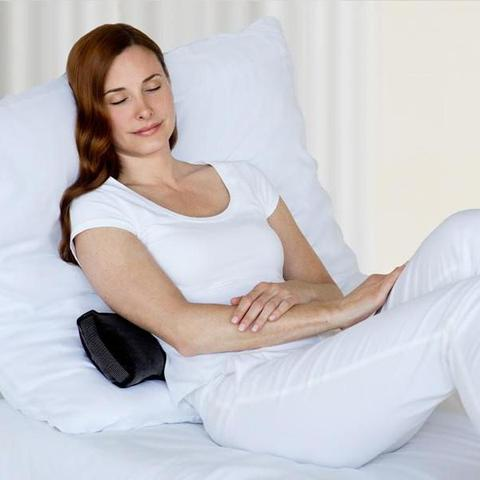 Woman sleeping with her back in Baxter Adjustable Back Pillow in cherry color.